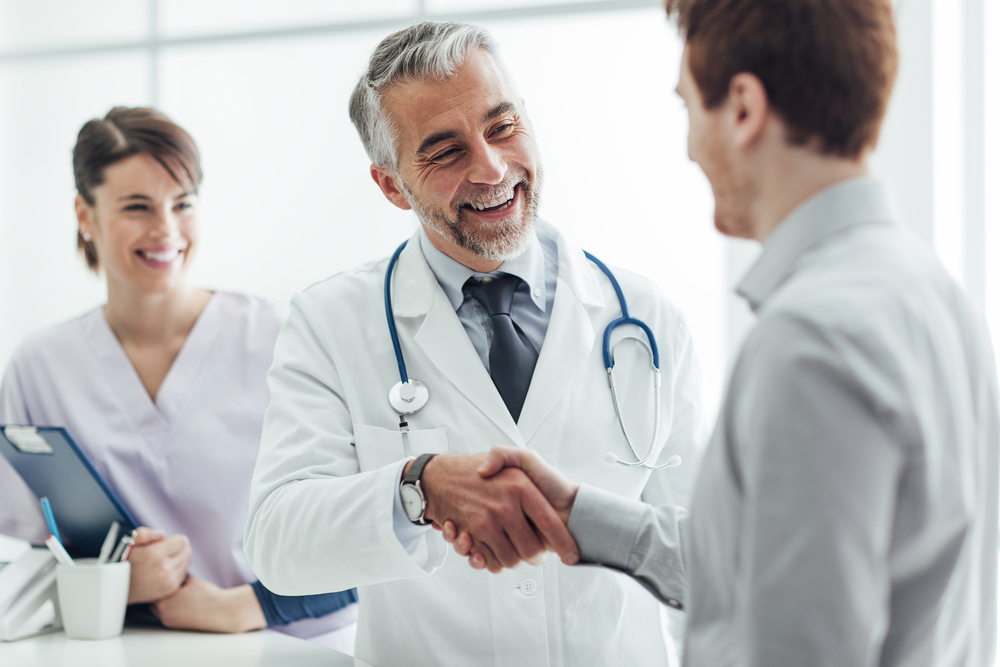 Doctor shaking hands with his patient and smiling